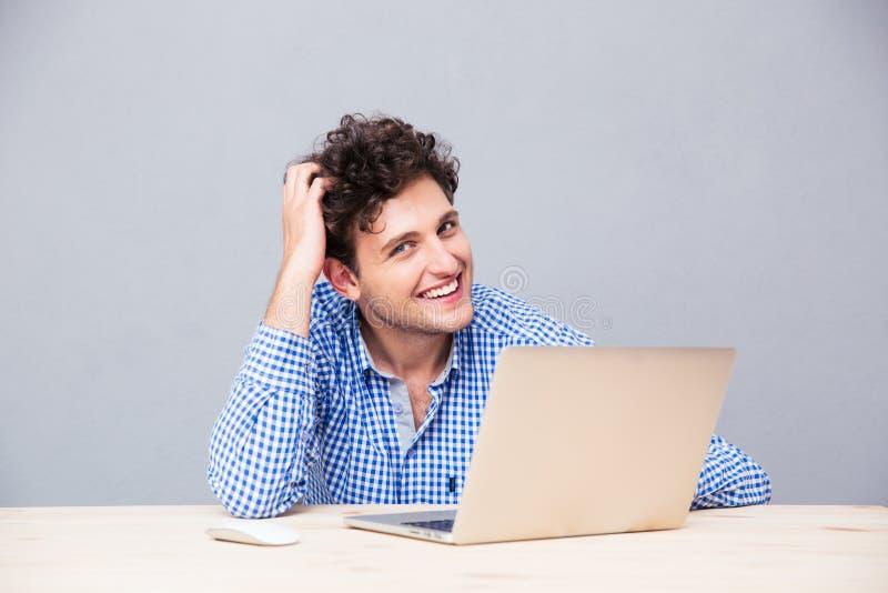 Hombre feliz que se sienta en la tabla con el ordenador portátil fotos de archivo libres de regalías