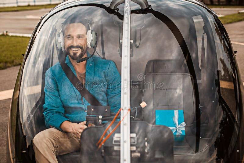 Hombre feliz que sonríe mientras que se sienta en cabina del helicóptero con su presente fotos de archivo libres de regalías