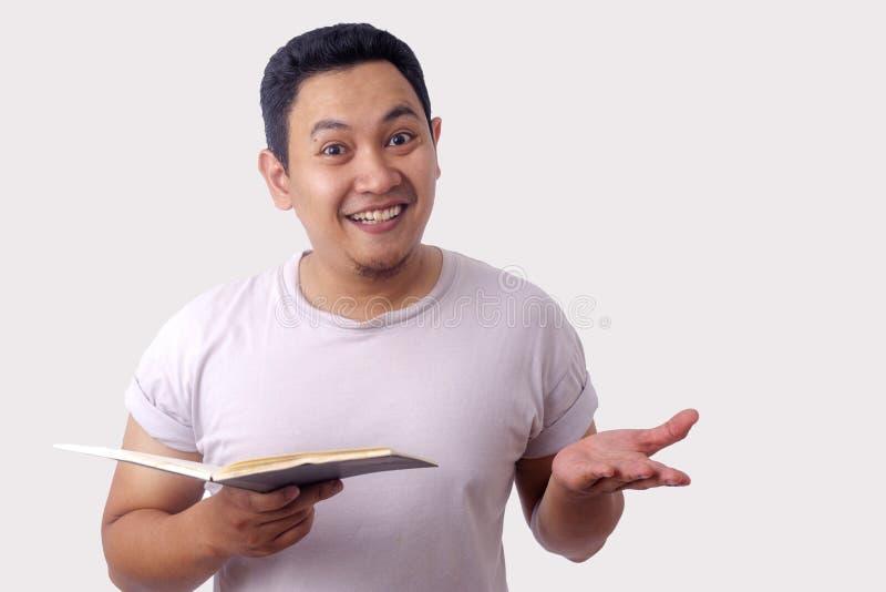 Hombre feliz que sonr?e mientras que libro de lectura imagenes de archivo