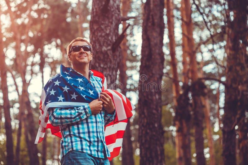 Hombre feliz que sostiene la bandera de los E.E.U.U. Celebración del Día de la Independencia de América 4 de julio Hombre que se  foto de archivo libre de regalías
