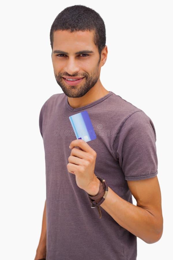 Hombre feliz que sostiene la tarjeta de crédito foto de archivo libre de regalías