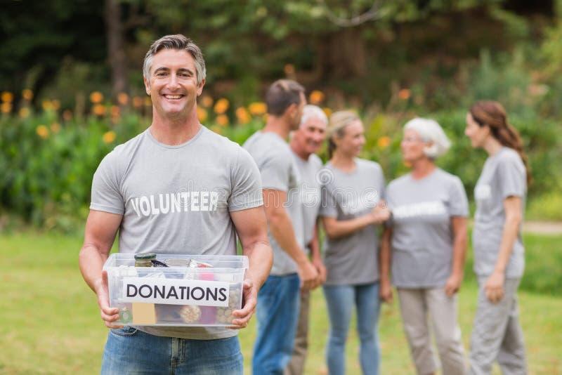 Hombre feliz que sostiene las cajas de las donaciones fotografía de archivo libre de regalías