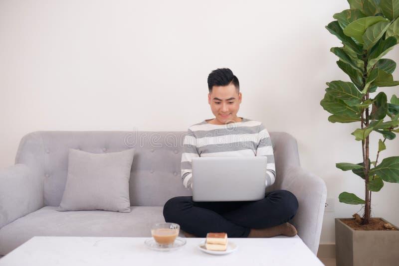 Hombre feliz que trabaja con el ordenador port?til y que come la torta en el sof? fotografía de archivo libre de regalías