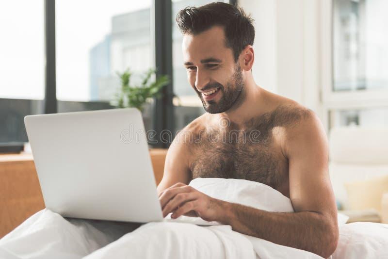 Download Hombre Feliz Que Usa El Ordenador Moderno En Cama Foto de archivo - Imagen de adminículo, nanómetro: 100534446