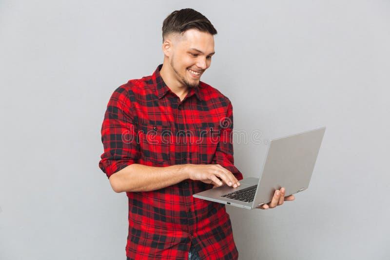 Hombre feliz que usa el ordenador portátil fotos de archivo libres de regalías