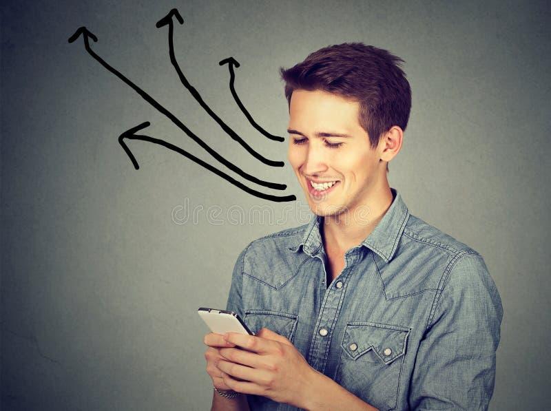 Hombre feliz que usa el teléfono móvil que manda un SMS enviando mensajes fotografía de archivo libre de regalías