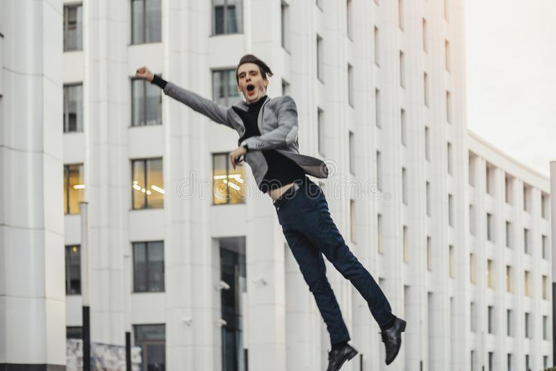 Hombre feliz que va a o desde trabajo y que baila al lado de centro de negocios foto de archivo