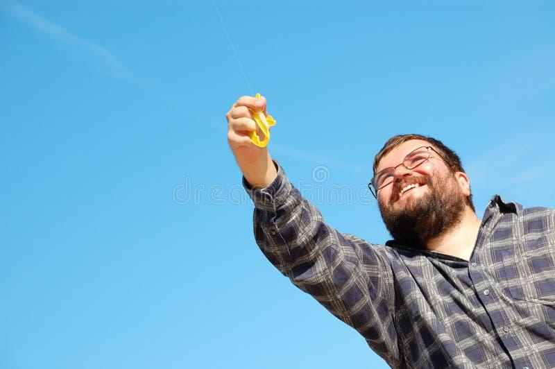 Hombre feliz que vuela una cometa imagen de archivo