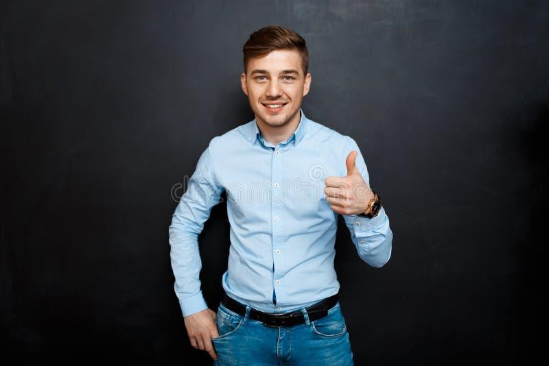 Hombre feliz sobre la pizarra Pulgares para arriba imagenes de archivo