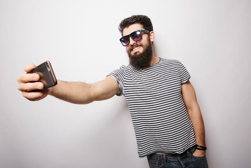 Hombre feliz sonriente del inconformista en vidrios de sol con la barba que toma el selfie con el teléfono móvil imagen de archivo