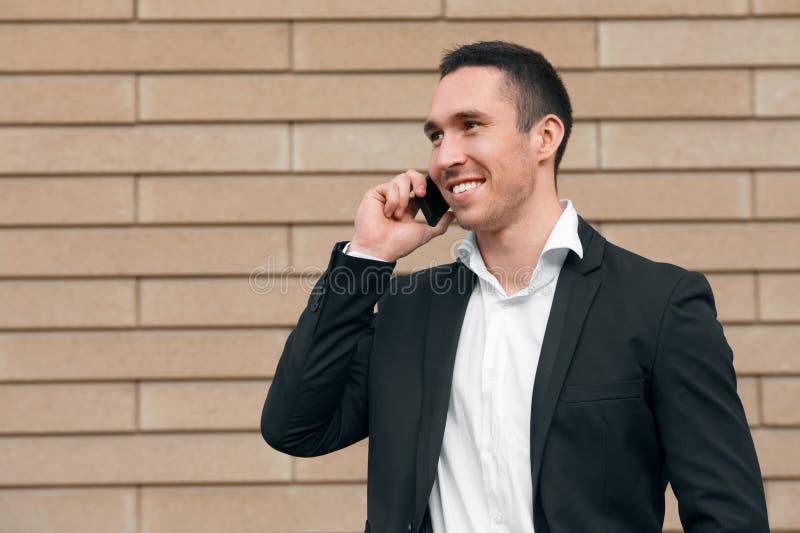 Hombre feliz sonriente que habla en el teléfono móvil en un traje negro, hombre moderno feliz outdoors imagenes de archivo