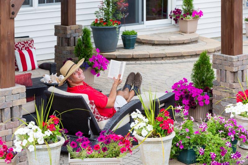 Hombre feliz sonriente que se relaja en su patio al aire libre imagen de archivo libre de regalías