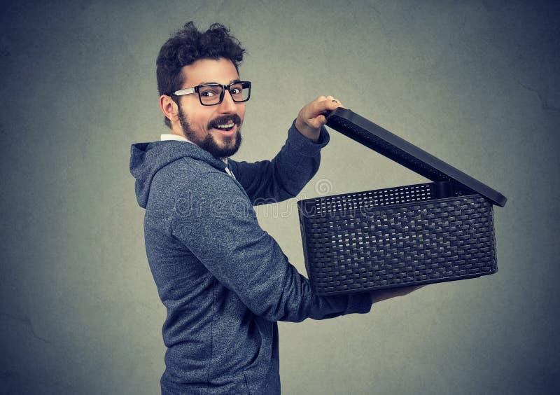 Hombre feliz sorprendente del inconformista en sudadera con capucha y vidrios que abren una caja con secreto imagen de archivo libre de regalías
