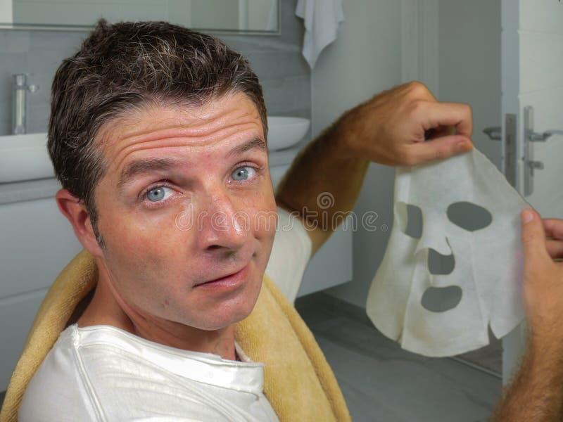 Hombre feliz y divertido joven en casa que intenta usando la máscara facial del papel de la belleza que limpia aprendiendo el tra imagen de archivo libre de regalías