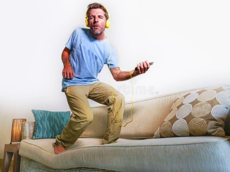 Hombre feliz y emocionado joven que salta en el sofá del sofá que escucha m foto de archivo