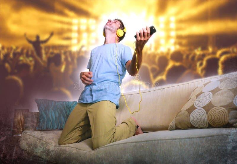 Hombre feliz y emocionado joven que salta en el sofá del sofá que escucha m fotos de archivo