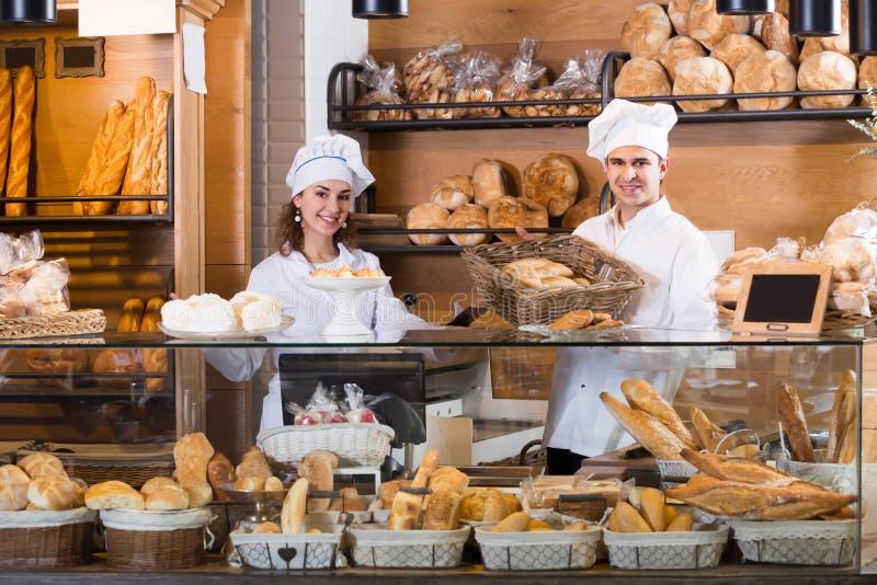 Hombre feliz y muchacha que venden los pasteles y los panes foto de archivo libre de regalías