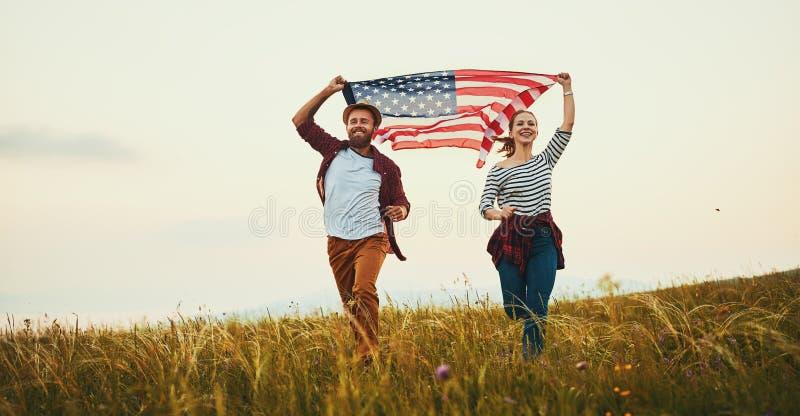 Hombre feliz y mujer de los pares con la bandera de Estados Unidos que disfrutan de la puesta del sol en la naturaleza foto de archivo