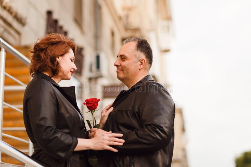 Hombre feliz y mujer de mediana edad que sostienen la rosa roja Amor en ciudad cita imagen de archivo libre de regalías