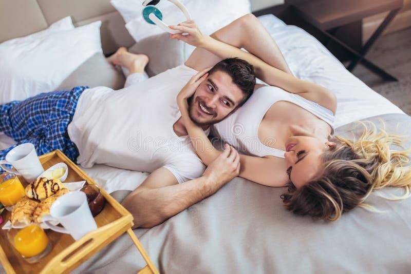 Hombre feliz y mujer que desayunan en cama fotografía de archivo libre de regalías