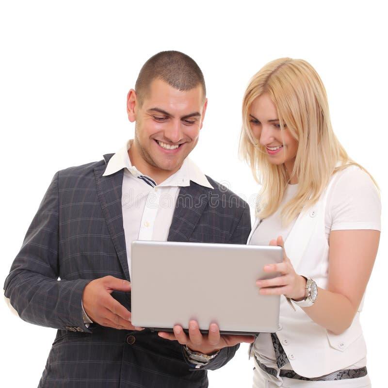 Hombre feliz y mujer que miran algo en el ordenador portátil imagen de archivo
