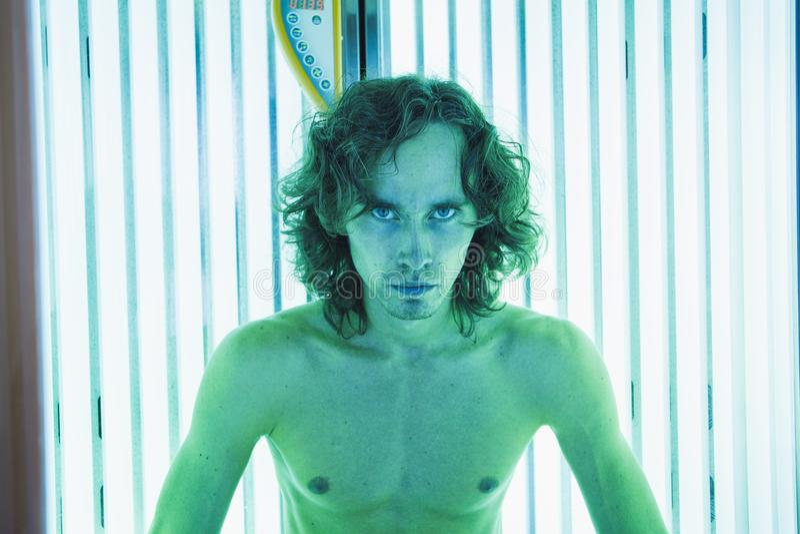 Hombre fino joven en el solarium en salón de belleza fotos de archivo libres de regalías