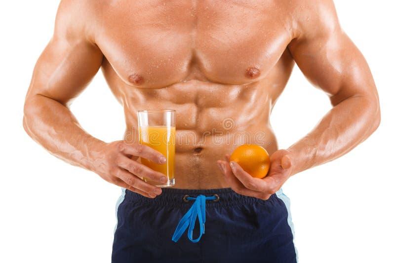 Hombre formado y sano del cuerpo que sostiene un jugo y una naranja, abdominal formada, aislados en blanco foto de archivo libre de regalías