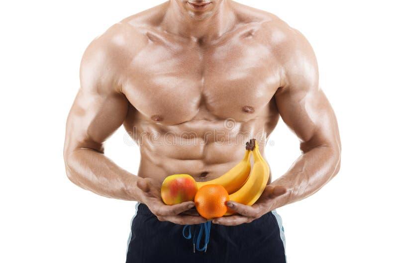 Hombre formado y sano del cuerpo sosteniendo las frutas frescas, abdominal formada, aisladas en blanco imagen de archivo