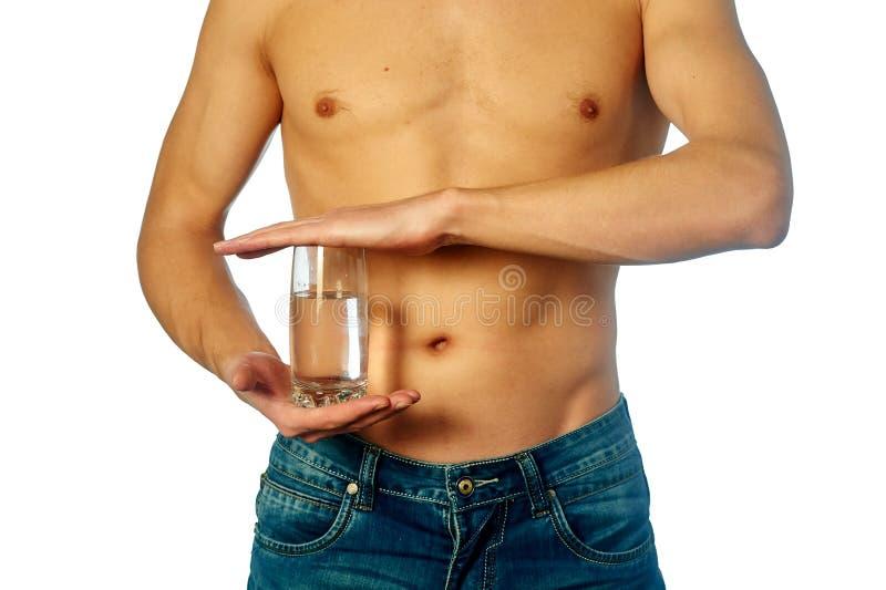 Hombre formado y sano que sostiene un vidrio de agua mineral foto de archivo libre de regalías