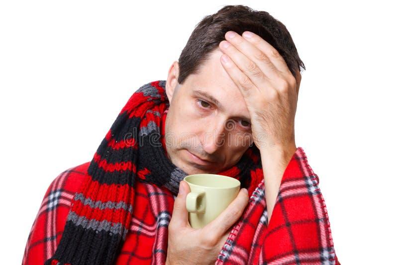 Hombre frío con la gripe, sosteniendo una taza foto de archivo