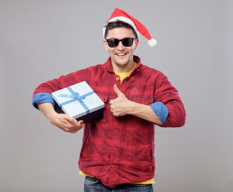 Hombre fresco joven con el sombrero y el regalo de Santa Claus fotos de archivo