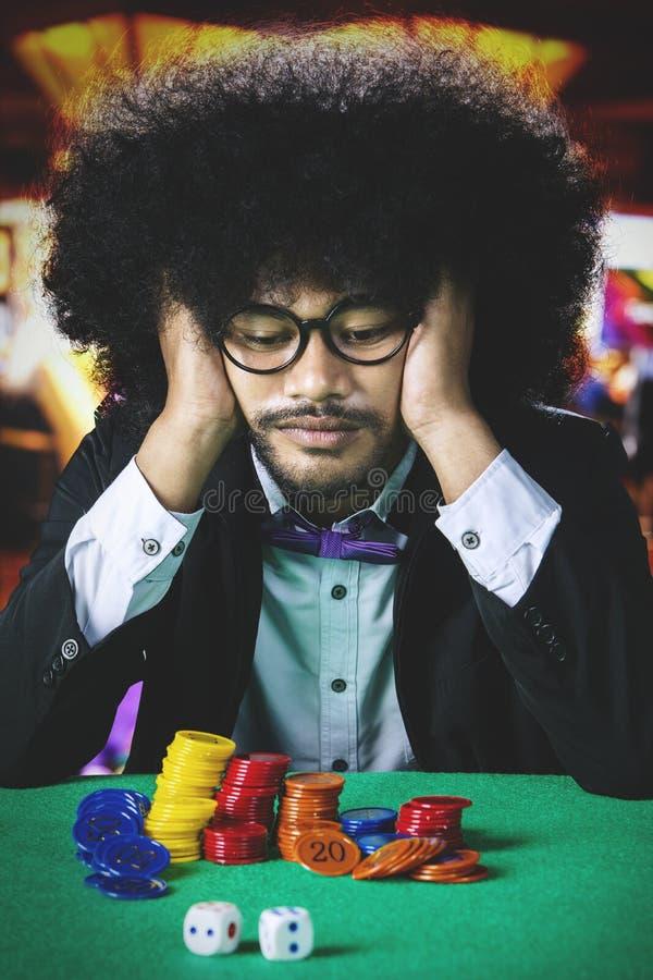 Hombre frustrado del Afro en casino imagenes de archivo