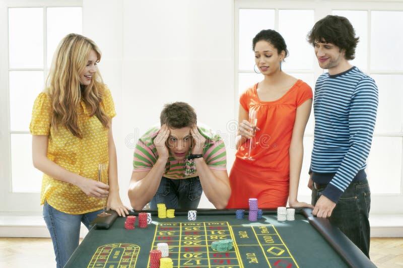 Hombre frustrado en la tabla de la ruleta con los amigos foto de archivo