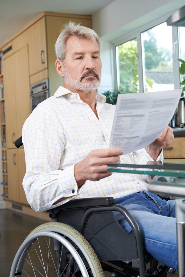 Hombre frustrado en silla de ruedas en casa que lee la letra fotos de archivo