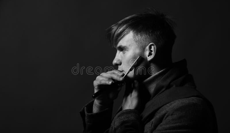 Hombre fuerte Cara brutal Peluqueros y concepto del estilo El hombre en estilo del vintage sostiene la maquinilla de afeitar imágenes de archivo libres de regalías
