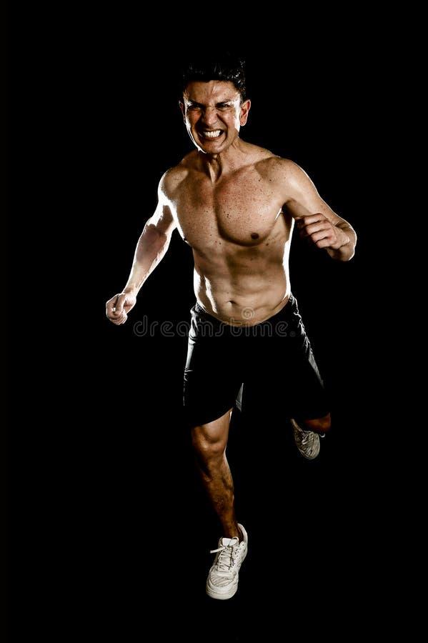 Hombre fuerte del ajuste con los músculos rasgados del cuerpo que funcionan con el torso desnudo duro resuelto del entrenamiento  imagen de archivo