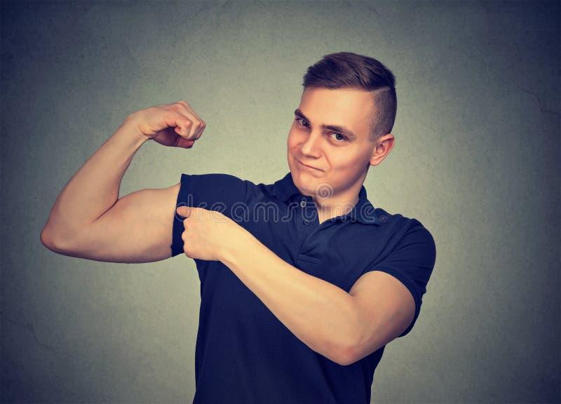 Hombre fuerte que dobla su bíceps foto de archivo