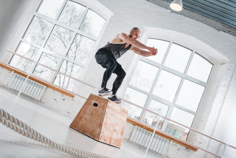 Hombre fuerte que hace ejercicios de salto sobre la caja en un gimnasio del estilo del entrenamiento cruzado foto de archivo libre de regalías