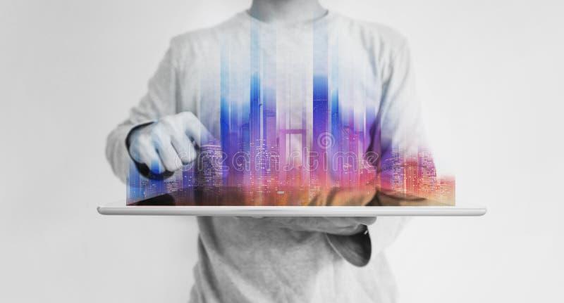 Hombre futurista que sostiene la tableta digital con el holograma constructivo moderno colorido imágenes de archivo libres de regalías