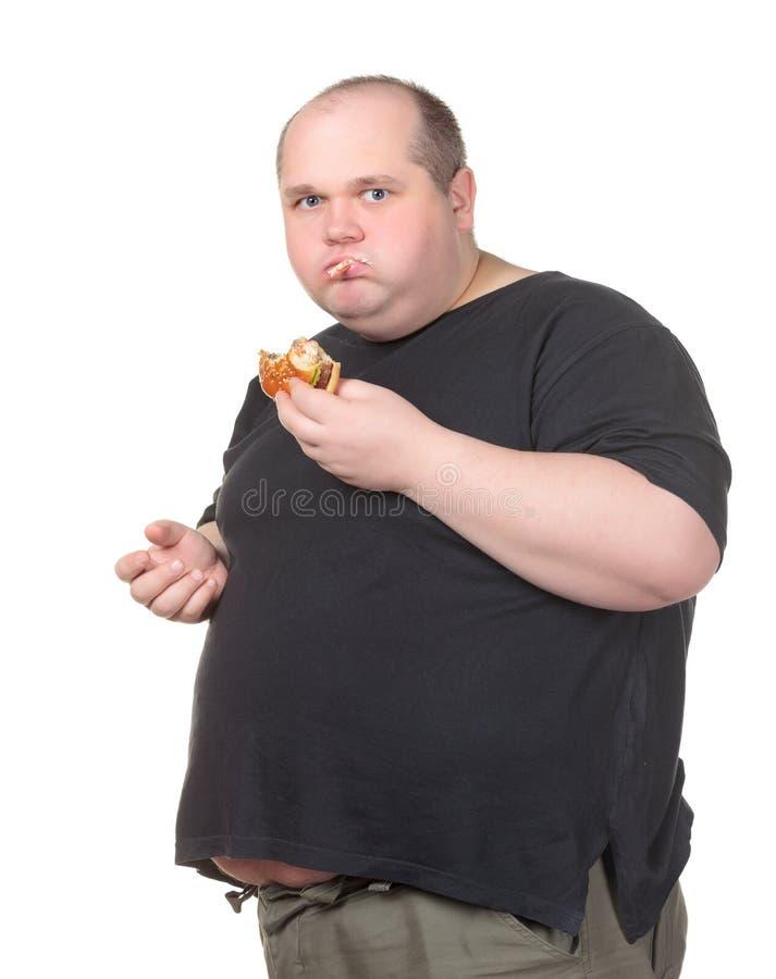Hombre gordo codicioso que come la hamburguesa fotos de archivo