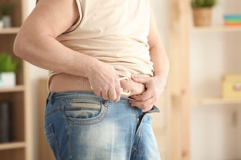 Hombre gordo con el calibrador de medición en casa, primer imagen de archivo libre de regalías