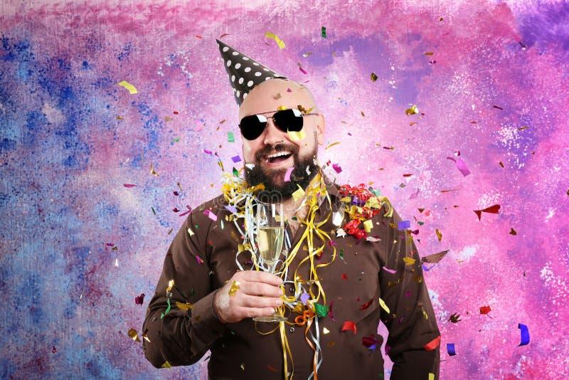 Hombre gordo divertido con el sombrero del partido y el vidrio de champán foto de archivo libre de regalías