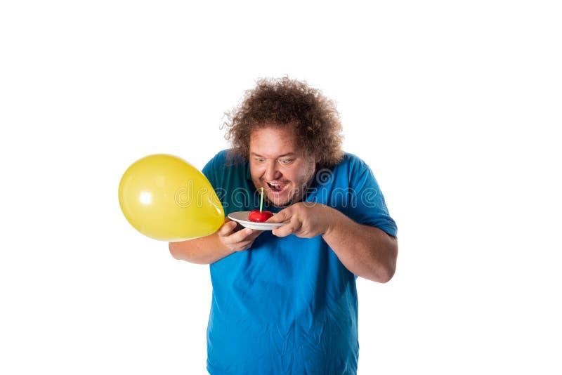 Hombre gordo divertido con la torta y los globos Feliz cumpleaños foto de archivo