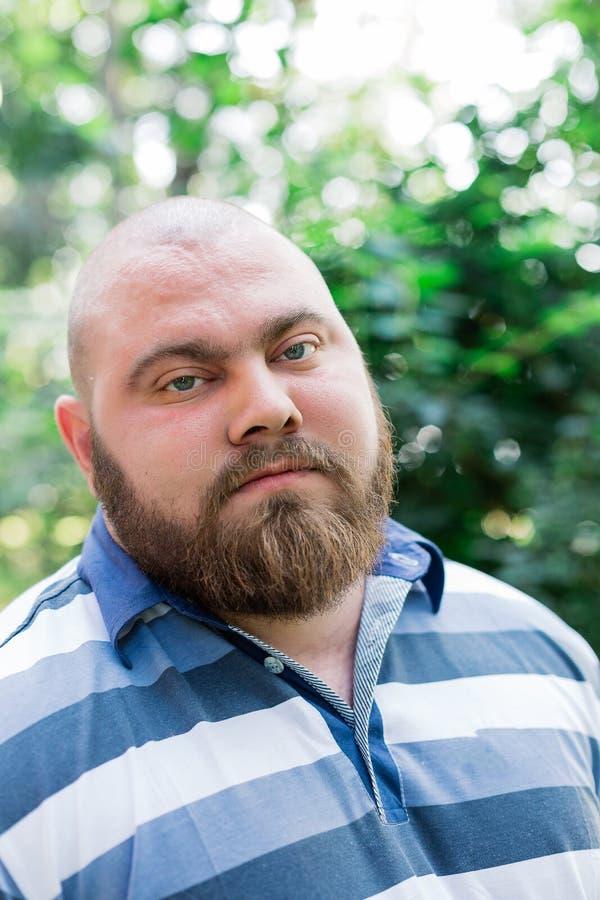 Hombre gordo en las miradas del parque en el marco, un retrato de un hombre con el exceso de peso fotos de archivo