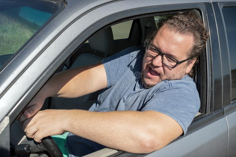 Hombre gordo enojado en el coche Camino y tensión foto de archivo libre de regalías
