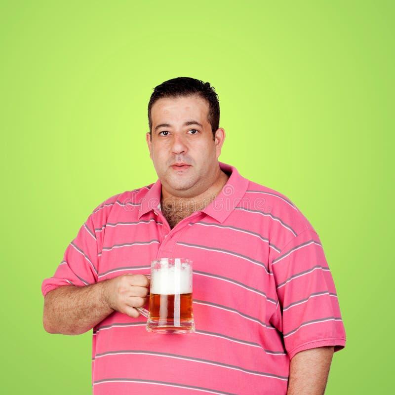 Hombre gordo feliz que bebe una cerveza imagen de archivo libre de regalías