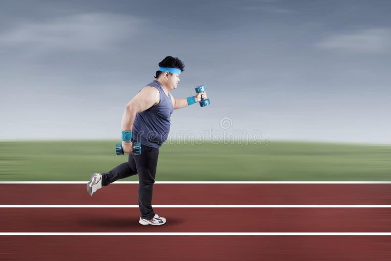 Hombre gordo que corre en la pista 1 imagen de archivo