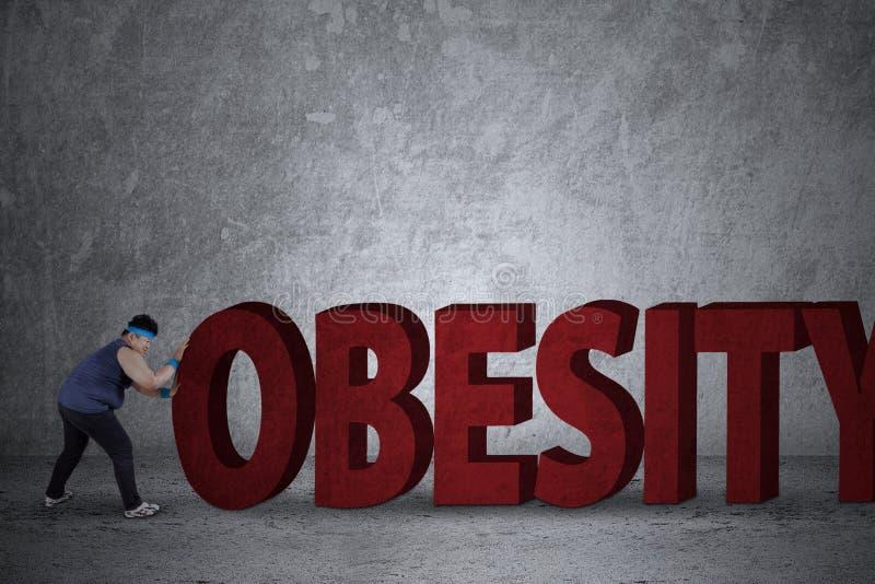 Hombre gordo que empuja una palabra de la obesidad imagen de archivo libre de regalías