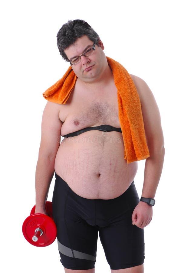 Hombre gordo que hace entrenamiento con pesas de gimnasia fotos de archivo