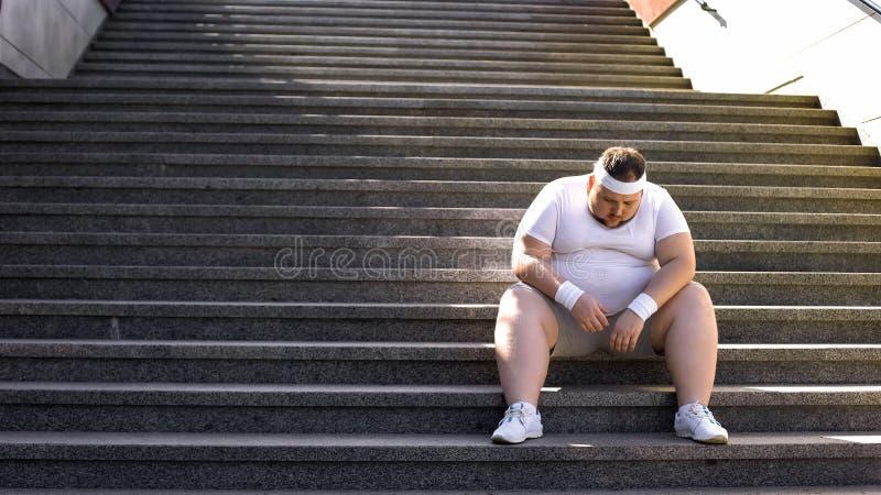 Hombre gordo que se sienta en las escaleras después de activar, ninguna fe en sí mismo, inseguridades foto de archivo